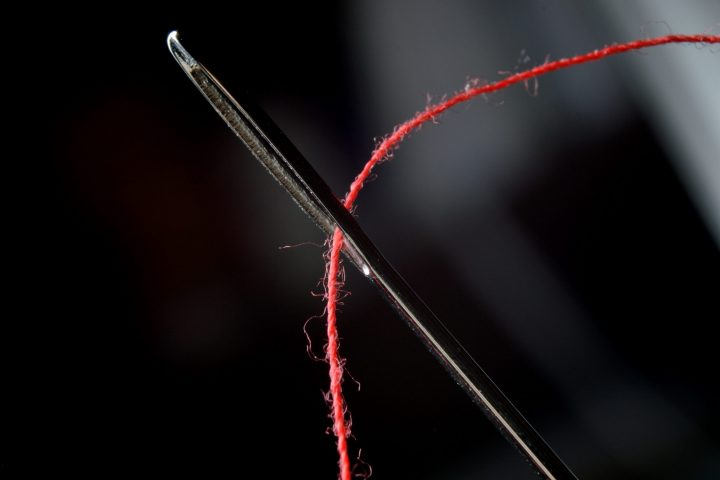 Needle and red thread on black background